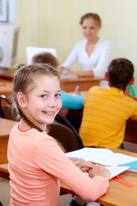 Portrait Of Lovely Girl At Workplace With Schoolboys And Teacher On Background