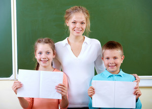 Portrait Of Cute Schoolchildren Showing Their Copybooks With Teacher Near By