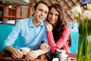 Portrait Of Amorous Young Couple Looking At Camera In Cafe