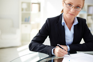 Young Businesswoman Signing Contract And Looking At Camera In Office