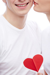 Close-up Of Amorous Young Girl With Red Paper Heart By Her Boyfriend Cheek