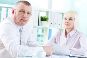 Portrait Of Serious Boss Looking At Camera At Workplace With Mature Woman Looking At Him On Background