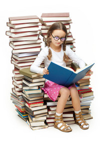 Portrait Of Diligent Pupil Sitting On Pile Of Books And Reading One Of Them