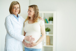 Happy Pregnant Woman And Her Doctor After Regular Examination At Hospital