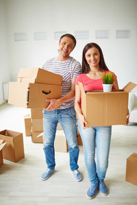 Happy Young Couple With Boxes Looking At Camera In New Flat