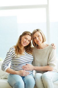 Happy Pregnant Woman And Her Mother Looking At Camera