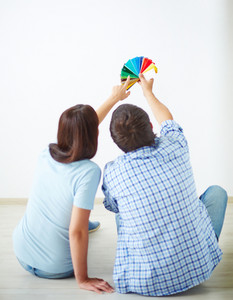 Rear View Of Young Couple Sitting On The Floor Of New House And Looking At Colorful Palette
