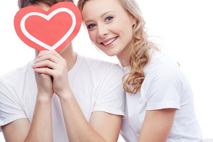 Portrait Of Happy Young Girl Looking At Camera With Her Boyfriend Near By Holding Red Heart By His Face