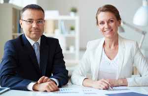 Two Mature Business Partners Looking At Camera In Office