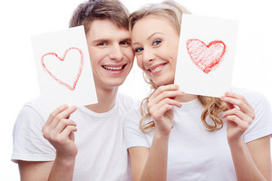 Portrait Of Young Amorous Couple Looking At Camera While Holding Papers With Hearts