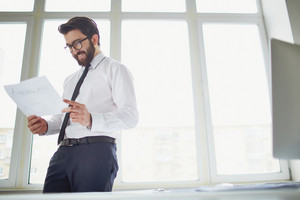 Smiling Businessman Standing By The Window In Office And Reading Paper