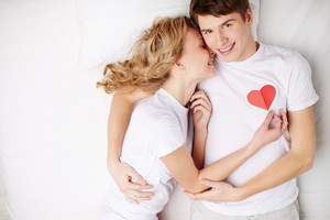 Portrait Of Happy Guy Looking At Camera While Embracing His Girlfriend Keeping Red Paper Heart By His Chest