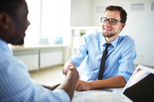 Image Of Two Young Businessmen Making Deal At Meeting In Office