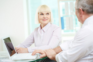 Portrait Of Happy Mature Businesswoman Looking At Her Partner During Discussion