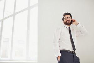 Portrait Of Elegant Businessman Speaking On Cellphone Indoors