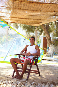 Happy Young Latino Man Spending Vacation At Summer Resort