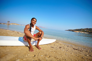 Happy Surfer Sitting On The Beach