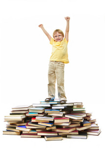 Portrait Of Cute Kid Standing On Pile Of Books With Raised Arms