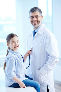 Cute Girl Examining Doctor With Stethoscope In Hospital