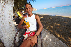 Happy Latino Man Having A Drink In Summer Cafe At Resort