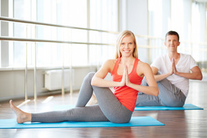Young Couple Doing Yoga Exercises In Fitness Club
