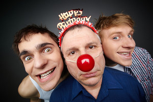 Two Guys Having Fun Playing Pranks On A Senior Man Celebrating Birthday Or Fool