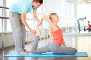 Man Helping A Woman With Yoga Position