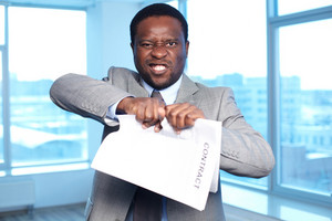 Portrait Of Angry African Businessman Tearing Contract And Looking At Camera