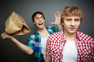 Crazy Guy Being Ready To Explode Paper Bag Behind His Friend Back