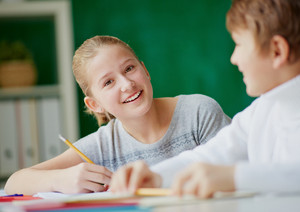 Image Of Cute Girl With Pencil Looking At Camera While Talking To Her Classmate