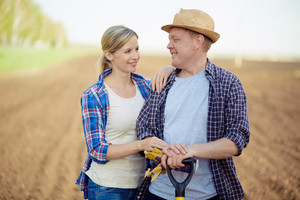 Image Of Two Happy Farmers Looking At One Another On Background Of Plowed Field