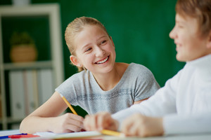Image Of Cute Girl With Pencil Talking To Her Classmate At Lesson