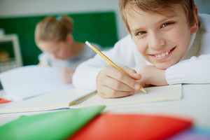 Portrait Of Cute Schoolboy Looking At Camera While Drawing