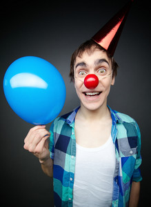 Happy Guy Holding A Balloon And Smiling Crazily At Camera Celebrating Fool