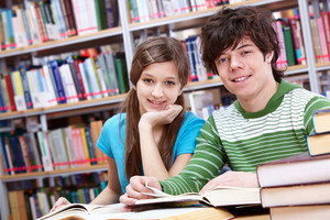 Portrait Of Teenage Girl And Her Classmate Looking At Camera In Library