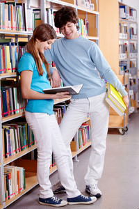 Portrait Of Teenage Girl Reading Book In Library With Her Classmate Near By