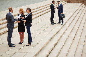 Two Small Groups Of Business People Interacting Outside