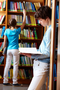 Two Teens Spending Time At Library Looking Through Books
