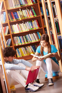 Portrait Of Teenage Friends Reading Books In Library