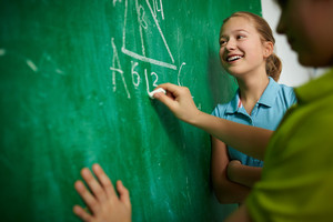 Happy Girl Looking At The Blackboard At Geometry Lesson With Her Classmate Near By