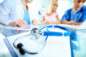Stethoscope And Document On Background Of Doctors And Patient Working With Laptop