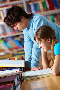 Young People Studying Together At Library Reading Books