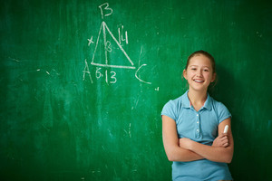 Portrait Of Clever Schoolgirl With Piece Of Chalk Standing By The Blackboard