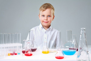 A Little Boy Looking At Camera With Liquids In Flasks Near By