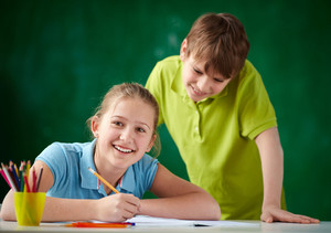Portrait Of Cute Schoolgirl Looking At Camera While Drawing At Lesson With Her Classmate Standing Near By