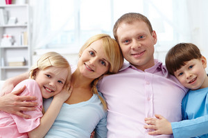 A Young Family Of Four Looking At Camera And Smiling While Relaxing At Home