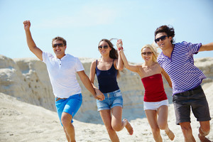 Ecstatic Young People Holding By Hands While Running Down Sandy Beach