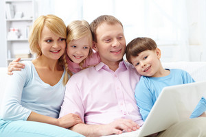A Young Family Of Four Sitting On Sofa And Looking At Laptop Screen