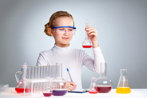 A Little Girl Looking At Chemical Sample In A Flask