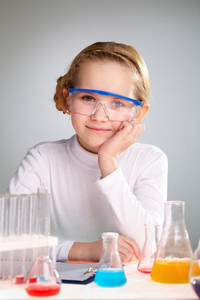 A Little Girl Looking At Camera With Chemical Samples In Flasks Near By